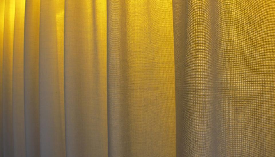 Detalje - det gule lys bag gardinet fremhæver stofligheden og skaber miljø