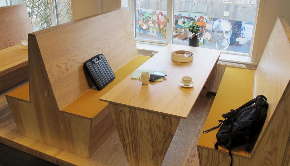Special designede borde og bænke danner et intimt rum i den store kantine