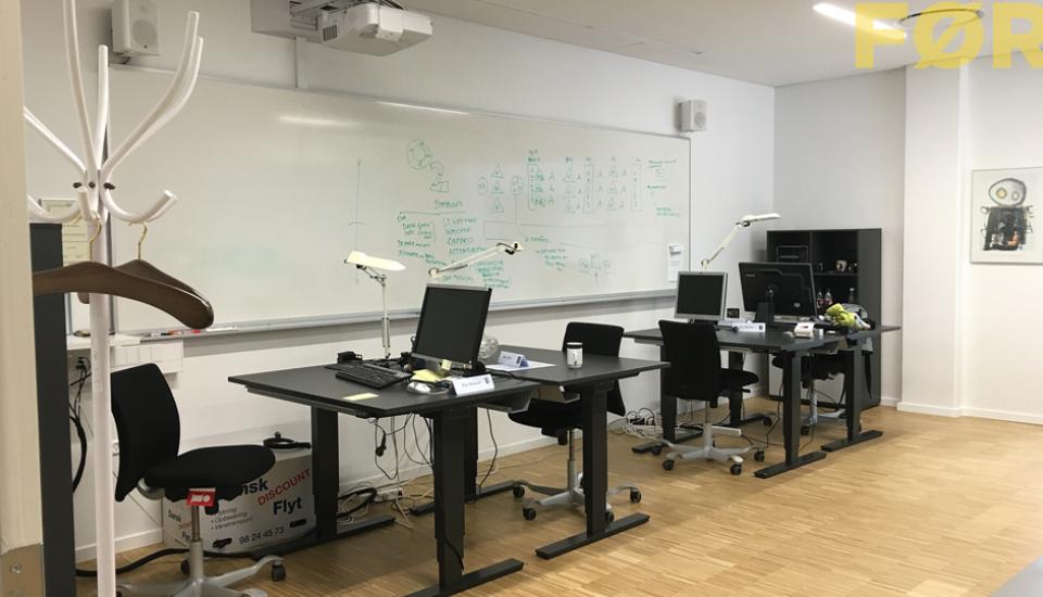 Møbleringen og funktionerne spænder ben for hinanden, whiteboardtavlen er gemt bag arbejdsbordene