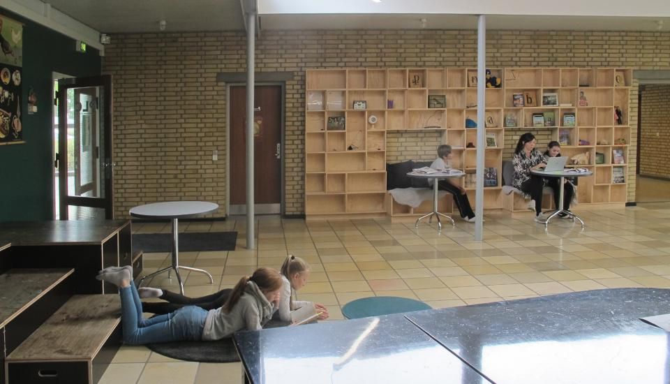 Udstillingsvæg med opholdsnicher og bløde gulvtæpper til ophold på gulvet giver mange måder for eleverne at opholde sig i rummet på